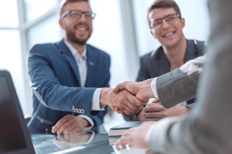 Personen geben sich in einem Beratungsgespräch die Hand
